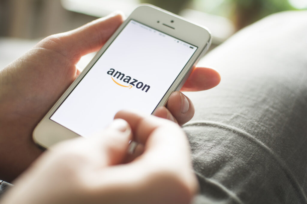 person holding phone with amazon logo on the home screen