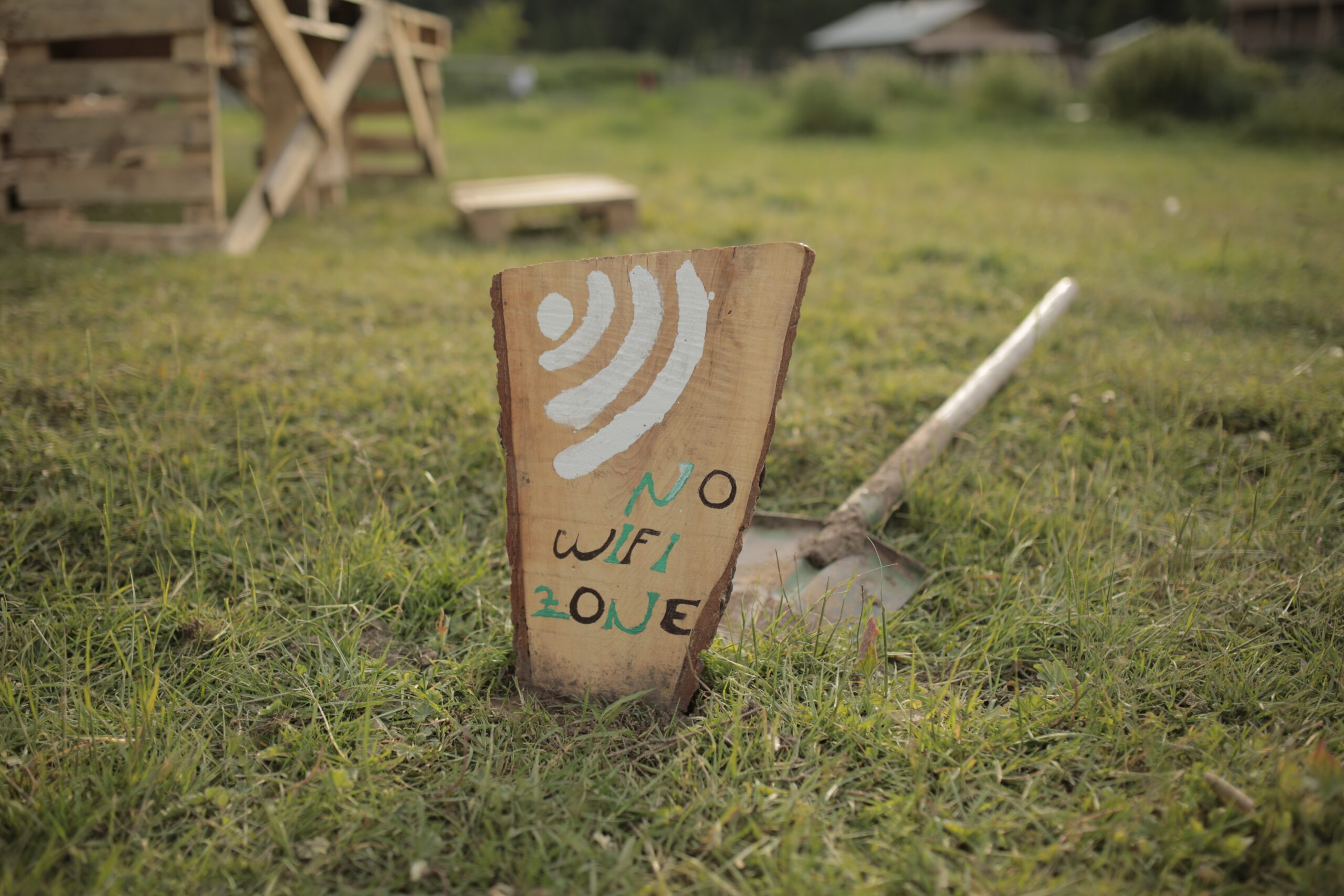 a wooden sign that reads: no wifi zone