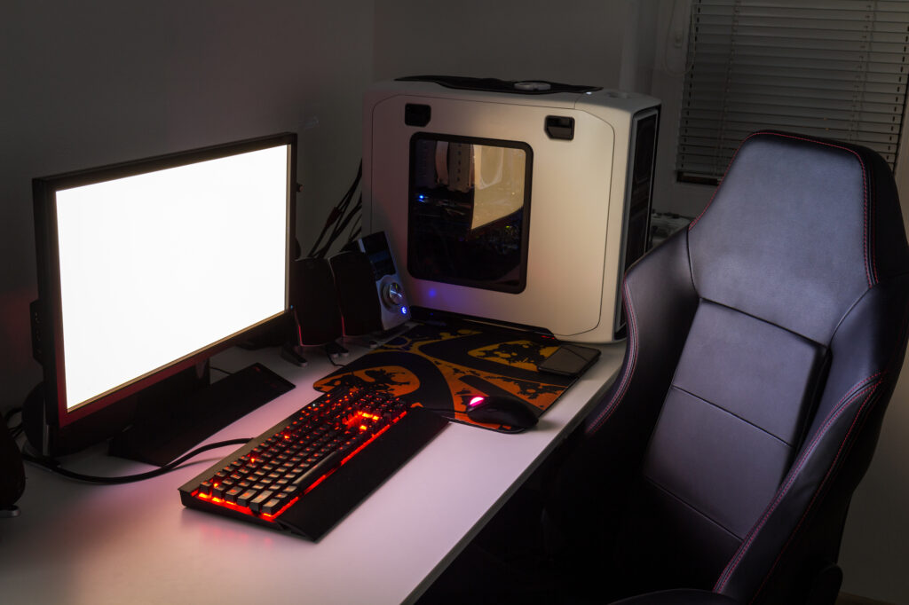 view of gaming monitor, keyboard, gaming chair, and gaming PC tower