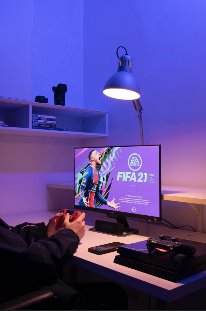 Person playing the soccer video game, FIFA 21, on their gaming computer