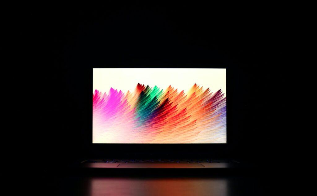 Computer monitor displaying colorful screen display in dark room