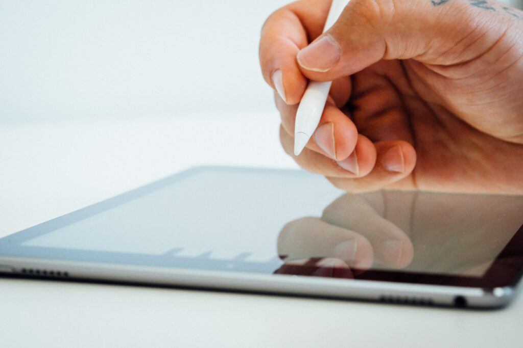 Hand using a stylus on a tablet.