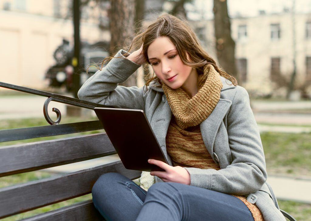 women sitting on park bench holding a tablet