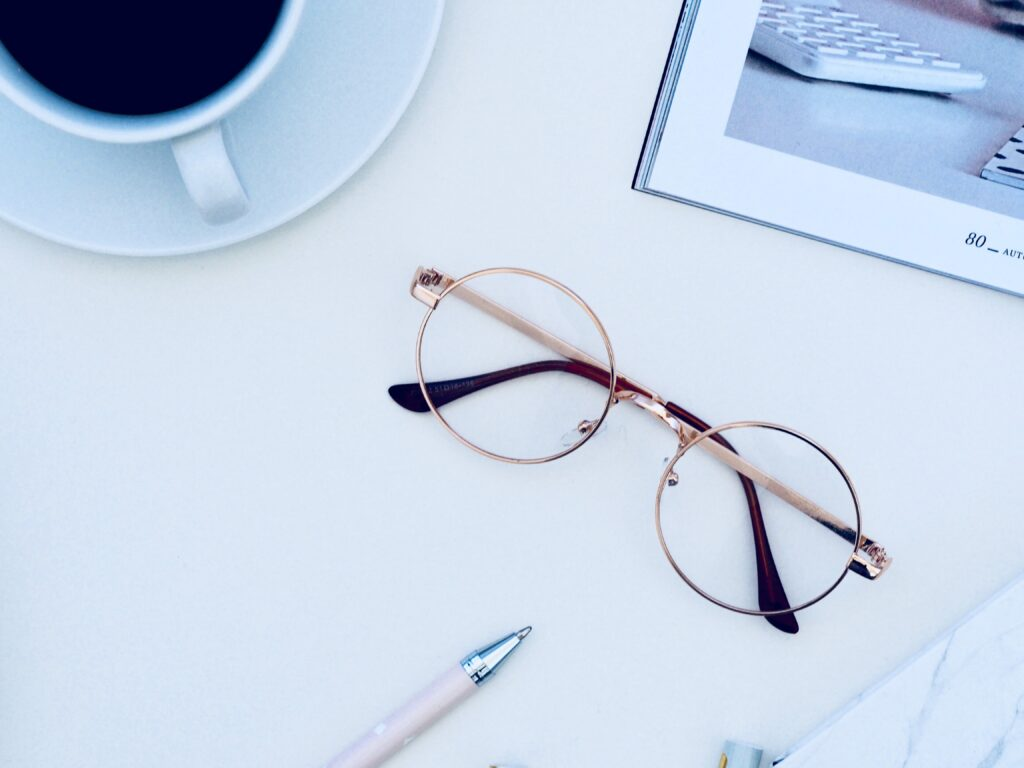 pair of glasses sitting on a white desk nexct to laptop and cup of coffee